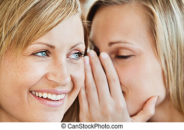 Blond young woman telling her friend a secret at home