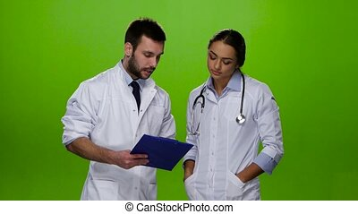 Doctor explains nurse what treatment the patient need -...