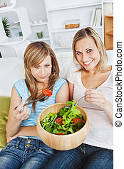 Hungry women eating a salad in the living-room