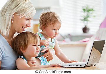 Astonished children looking at a laptop with their mother