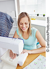 Bright woman sewing clothes in the kitchen at home