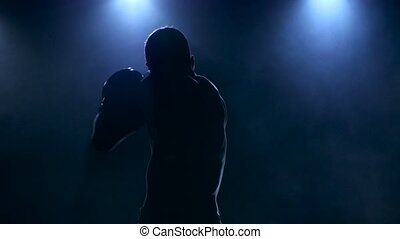 Silhouette strong muscular body of a boxer in a smoke -...