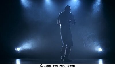 Coaching boxer male in a dark studio with rear lights -...