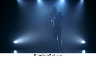 Strong and muscular body of a boxer in silhouette...
