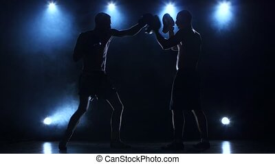 Two boxers are working to blows. Silhouette of young...