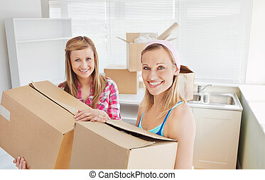Bright female friends holding boxes