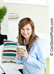 Captivating blond businesswoman holding a coffee sitting on...