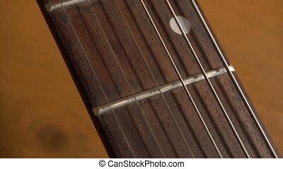 Camera slowly sliding over electric guitar - Camera slowly...