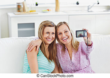 Laughig female friends doing pictures of themselves