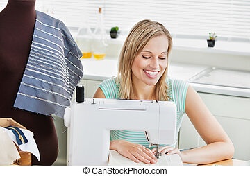 Radiant woman sewing clothes at home in the kitchen