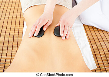 Close-up of a caucasian woman receiving a back massage with hot stone in a health spa