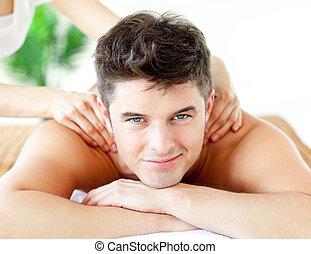 Handsome smiling man enjoying a back massage