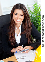 Beautiful businesswoman using calculator smiling at the camera