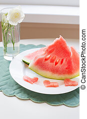 on the table is a piece of watermelon on a white plate