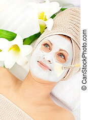Captivating young woman receiving white cream on her face in...