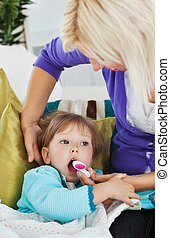 Sick little girl getting syrup from her caring mother at...