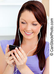 Charming woman listen to music using her cellphone at home