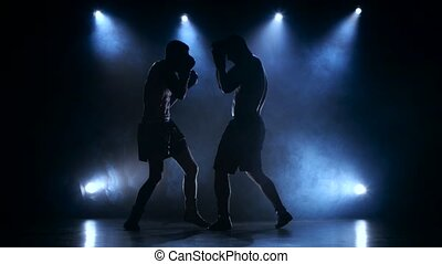 Two young sportsman are boxing in the studio