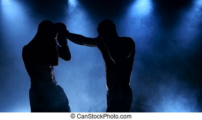 Boxing two young sportsman in a smoky studio in silhouette,...