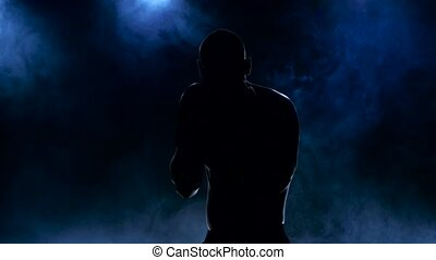 Silhouette of boxer who trains strike blows, strong body man...