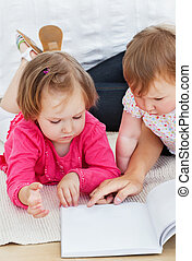 Concentrated children reading a book with their mother