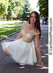 girl with brown hair in a bright dress is walking in a summer park