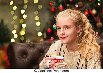 13 years old teen girl in warm sweater sitting on sofa in...