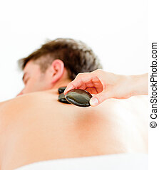 Close-up of a positive young man having a back massage with hot stone in a spa center