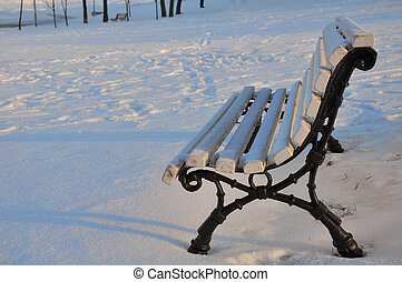 bench in snow in the city park early in the morning
