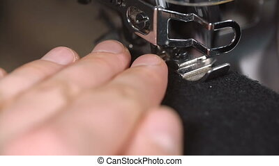 a worker sews on the sewing machine Closeup