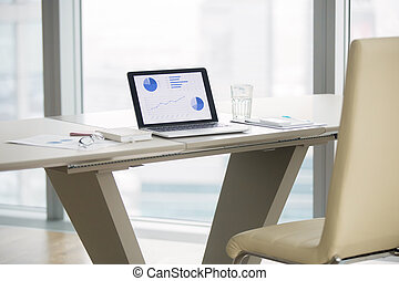 Laptop on a modern office desk - Laptop with graphs on...