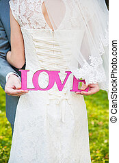 Pink sign of love with the bride's back