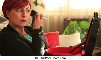 Attractive middle aged woman applying make up - Portrait of...