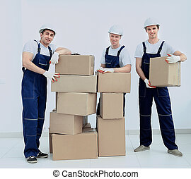 stevedores unload boxes in new premises - Group of...