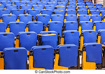 Rows of blue seats in lecture hall.