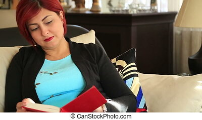 Middle aged woman reading a novel at home