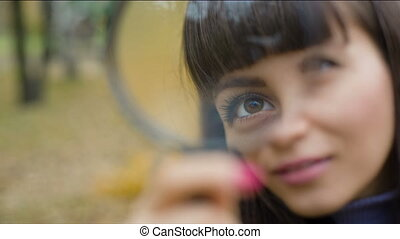 Woman's eye looking through a magnifying glass