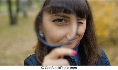 Woman looking through a magnifier - Young woman friendly...