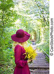 girl in a hat with a bouquet of yellow flowers
