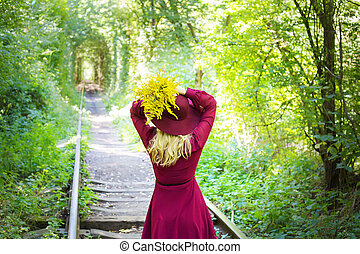 girl in a hat with a bouquet of yellow flowers in the forest