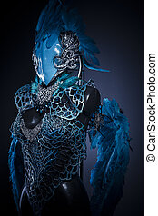 Feathers, Handmade styling of a bird or mythological figure with blue wings and pieces of metal and precious stones