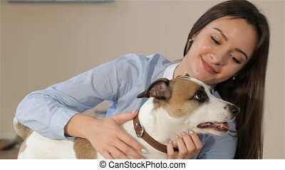 Woman pets the dog at the veterinarian clinic - Pretty...