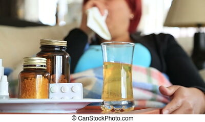 Sick woman sneezing into tissue at home - Ill red hair woman...