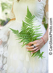 girl in a white dress, holding a green fern leaves in the...