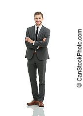 portrait in full length of a smiling young businessman with a st