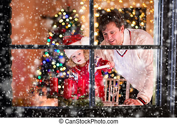 Father and daughter lighting Christmas candles - Christmas...
