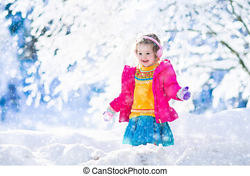 Child playing in snowy winter park