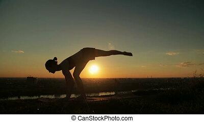 Woman doing Ashtanga yoga in the park at sunset