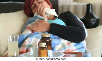 Woman at home sick with flu lying on bed and resting -...