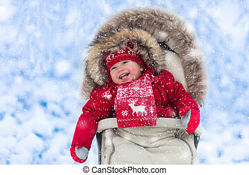 Baby in stroller in winter park with snow - Happy laughing...